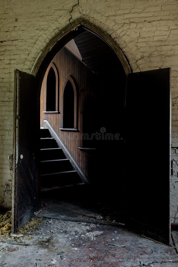 对木头被镶板的走廊的被成拱形的词条-崩溃,被放弃的教会 免版税库存照片