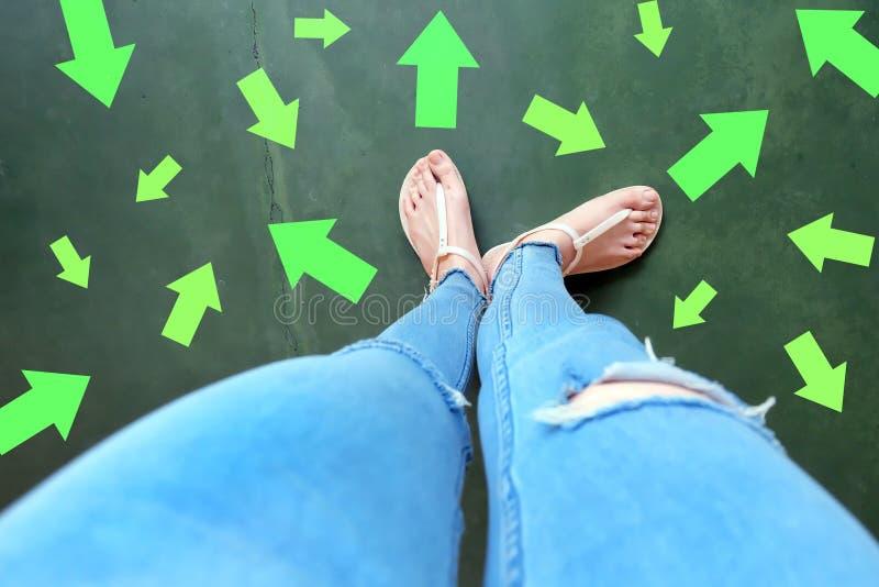 对未来的不同的方向箭头 在站立与绿色箭头线选择的妇女上的Selfie 鞋子妇女鞋类和ar 库存照片