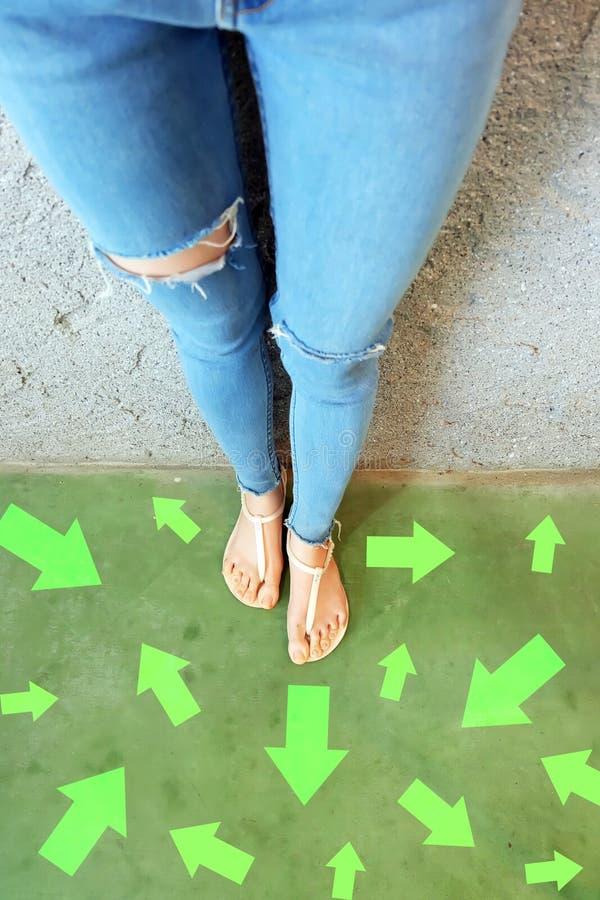 对未来的不同的方向箭头 在站立与绿色箭头线选择的妇女上的Selfie 鞋子妇女鞋类和ar 库存图片