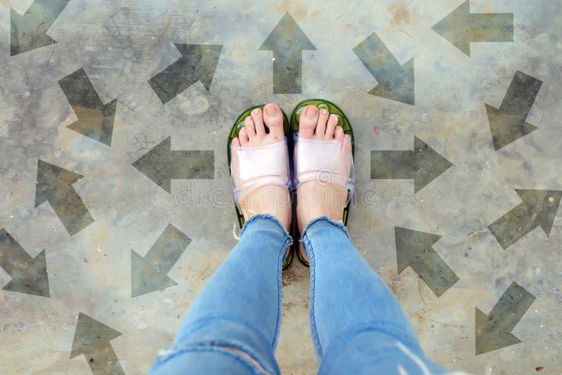 对未来的不同的方向箭头 在站立与绿色箭头线选择的妇女上的Selfie 鞋子妇女鞋类和ar 免版税图库摄影
