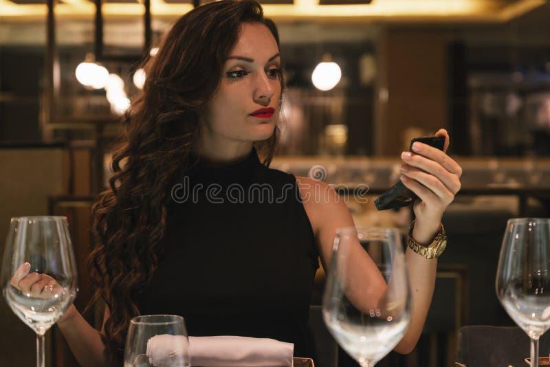 对构成的有吸引力的女性用途镜子在餐馆 免版税库存照片