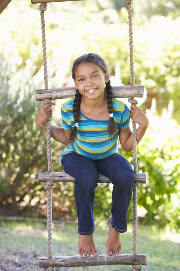 对树上小屋的女孩上升的绳梯 免版税库存图片