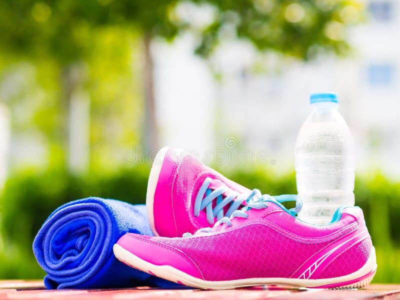 对桃红色体育穿上鞋子毛巾在木板的水瓶 在背景森林或公园足迹 免版税库存图片