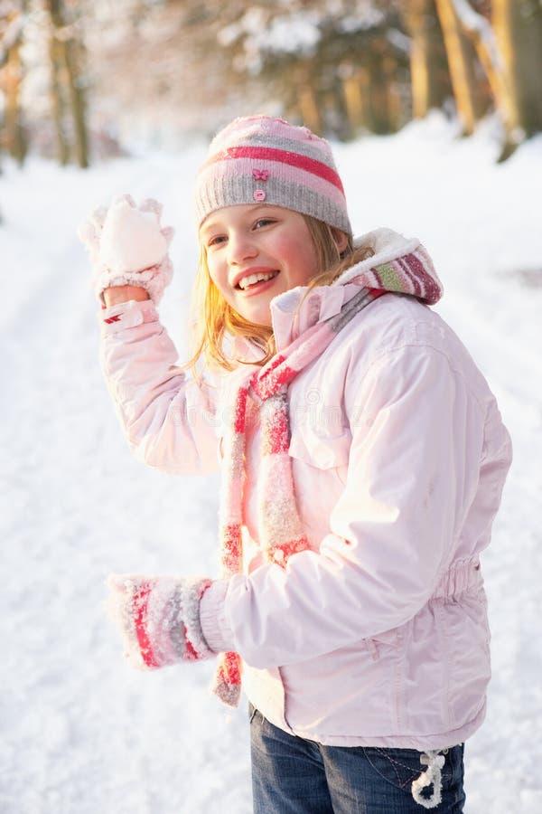 对森林地的女孩雪球多雪的投掷 库存照片