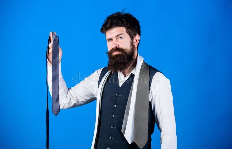 人有胡子的行家举行在蓝色背景的少量领带 有选择领带的胡子的人 完善的领带 对正式 免版税库存照片