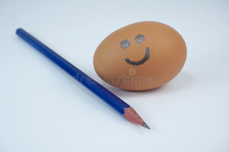 对此与微笑的红皮蛋画的与一支锋利的铅笔 库存照片