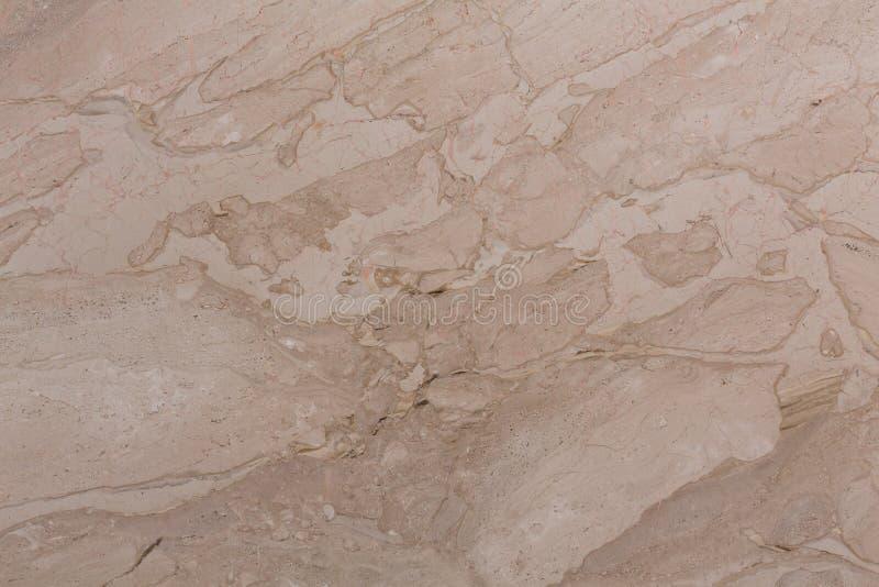对比与镇压的轻的米黄大理石纹理表面上 免版税图库摄影