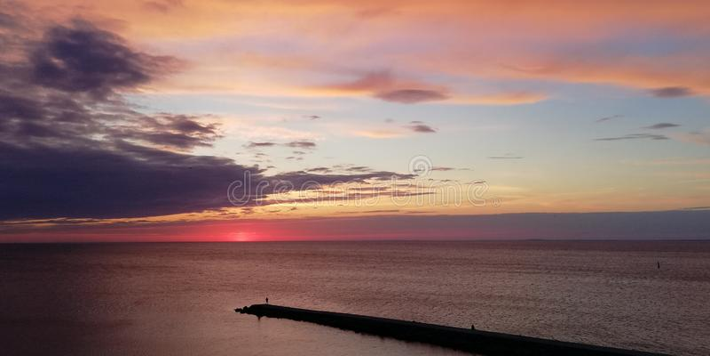 对比令人激动的背景 海晚上在桃红色,蓝色和紫色颜色的日落风景 与人剪影的长的石购物中心 免版税库存图片