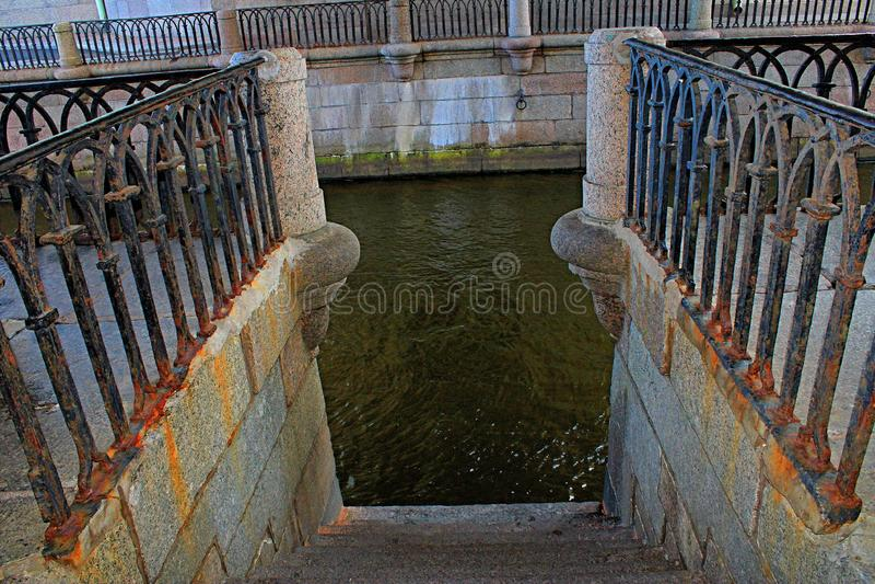 对水的下降由从堤防的台阶与生锈的栏杆 免版税库存图片