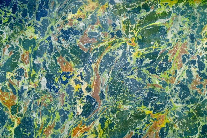 对水的抽象大理石作用,称ebru 混杂的黄色,蓝色和绿色 库存照片