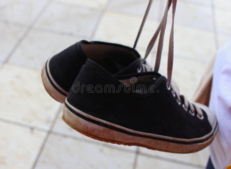 对污浊的黑运动鞋 免版税库存图片