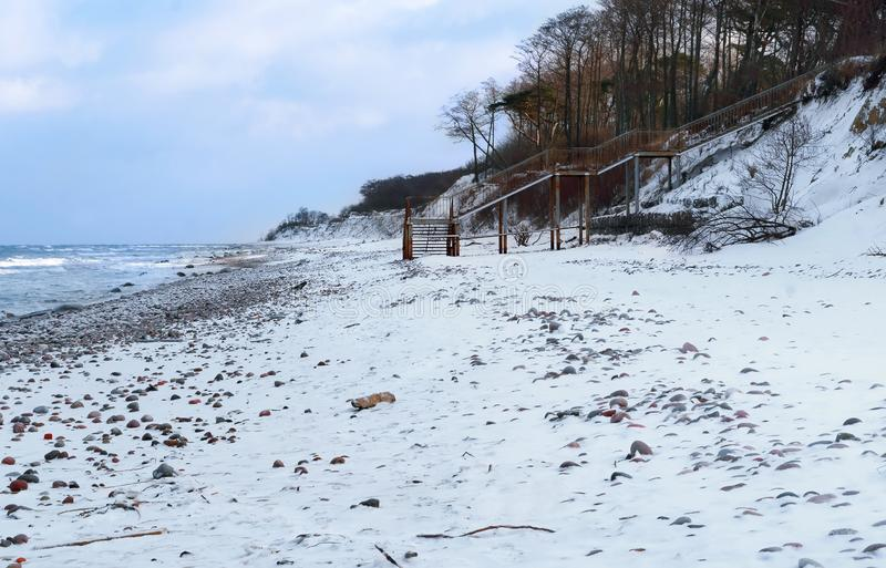 对海和雪的下降在海滩 免版税库存照片