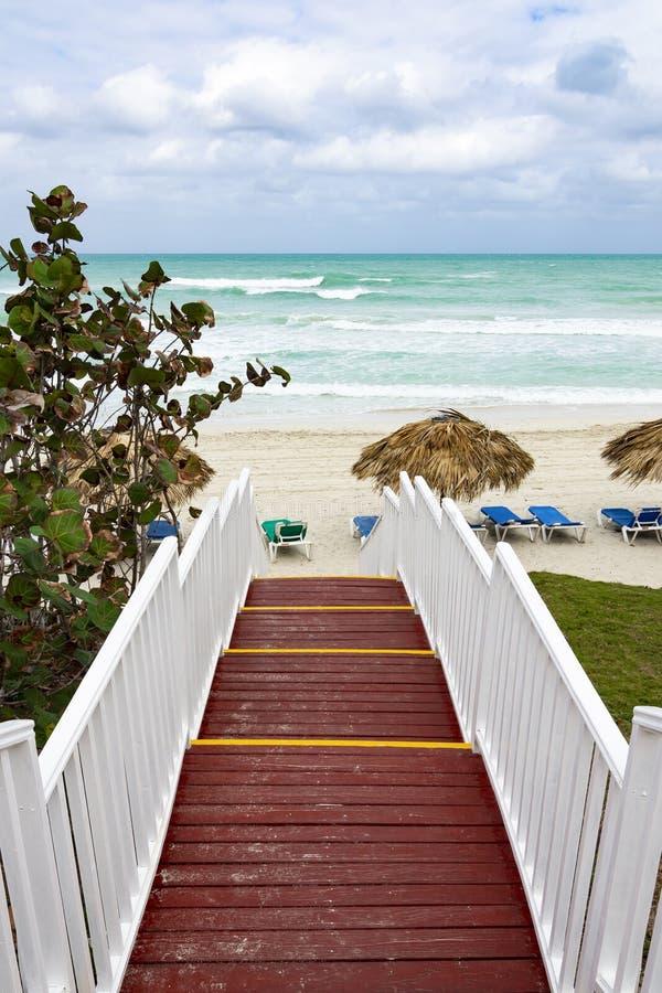 对海洋海滩的美丽的木梯子 与秸杆伞和太阳懒人的海滩 多云天空和大海 免版税库存照片