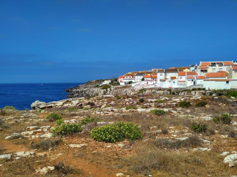 对海湾的看法与岩石和房子在Peniche,葡萄牙 库存照片
