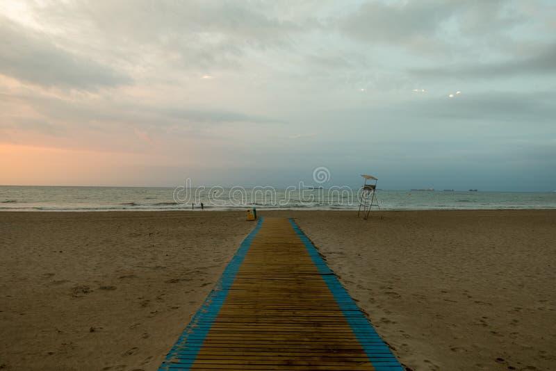 对海滩的走道在美好的日出 免版税库存照片