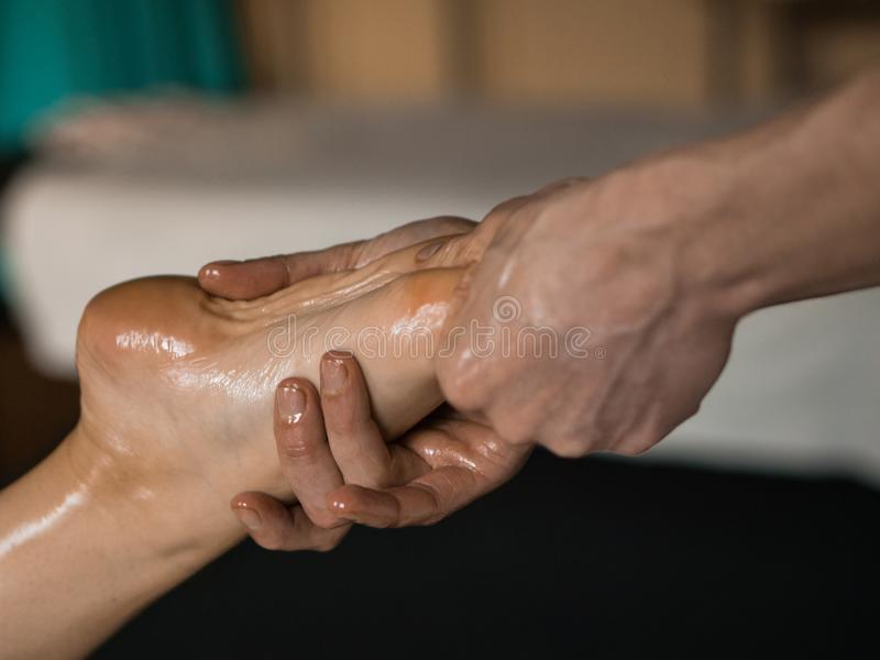 对深组织被上油的按摩做的专业男按摩师女孩在Ayurveda按摩会议 库存图片