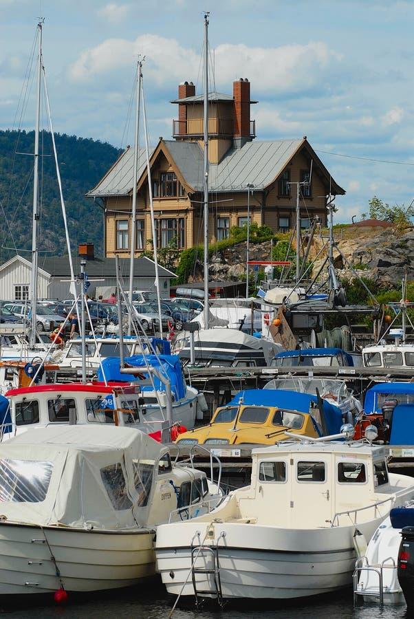 对港口有小船的被栓和一个历史大厦的看法在背景在Drobak,挪威 库存图片