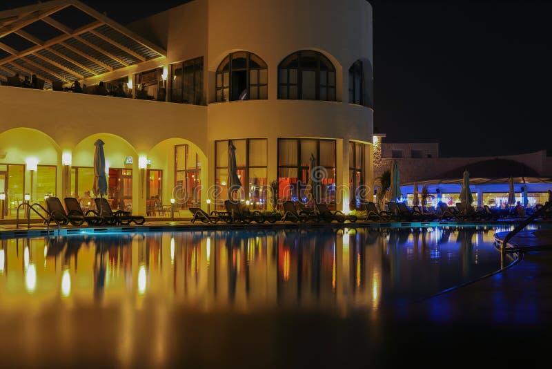 对游泳场和棕榈树的夜视图在红海附近的海滩在沙姆沙伊赫,南西奈,埃及 免版税库存图片