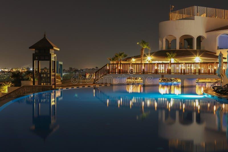 对游泳场和棕榈树的夜视图在红海附近的海滩在沙姆沙伊赫,南西奈,埃及 库存照片