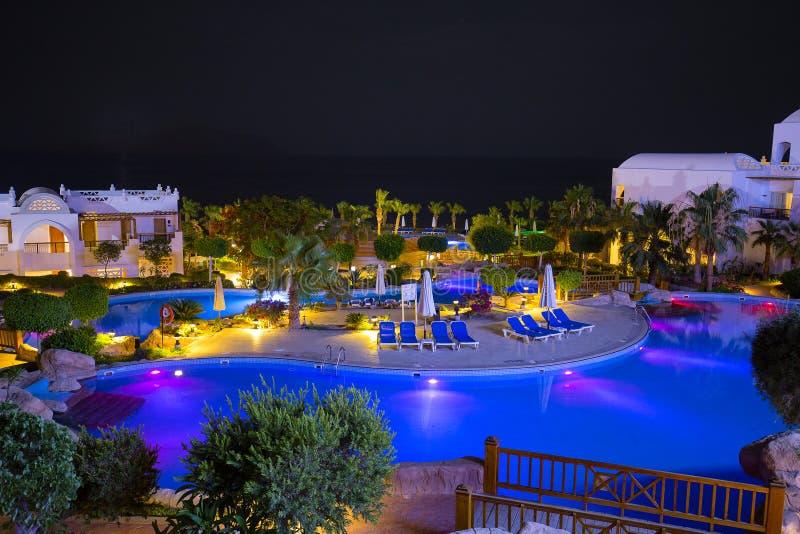 对游泳池、大厦和棕榈树的夜视图在红海附近的海滩在Sharm El谢赫,南西奈,埃及 免版税库存图片