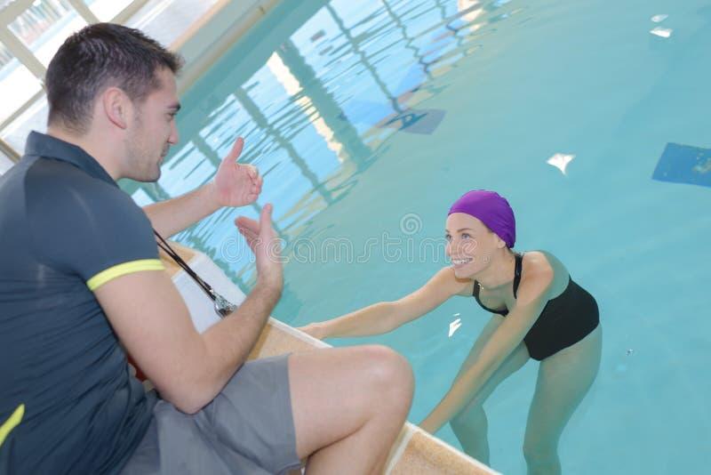 对游泳者女孩的Coachtranier水池的谈论与athlet 免版税图库摄影