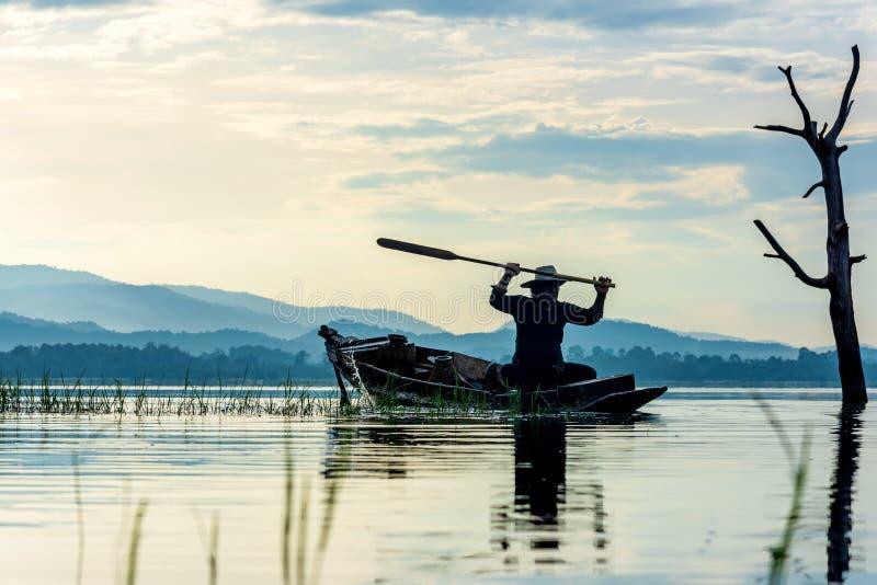 对湖的渔夫行动阳光早晨和剪影渔夫的室外在小船, 图库摄影
