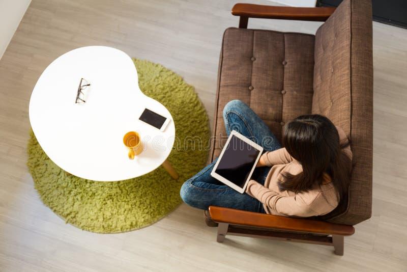对片剂个人计算机和的妇女用途顶视图坐沙发 免版税图库摄影