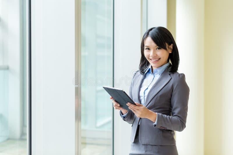 对片剂计算机的亚洲女商人用途 免版税库存照片