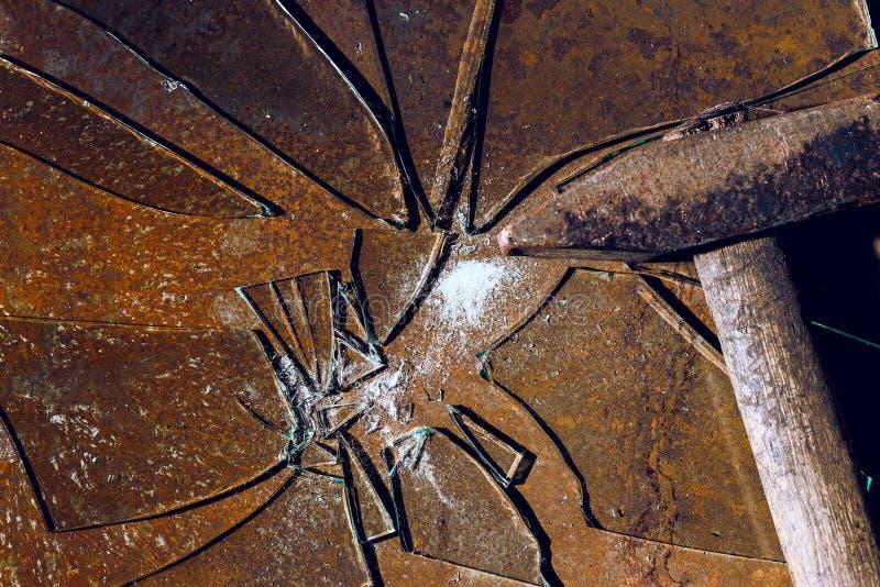 对片断的残破的玻璃在一根生锈的金属板 在它旁边是有木把柄的一把老锤子 纹理 免版税库存照片