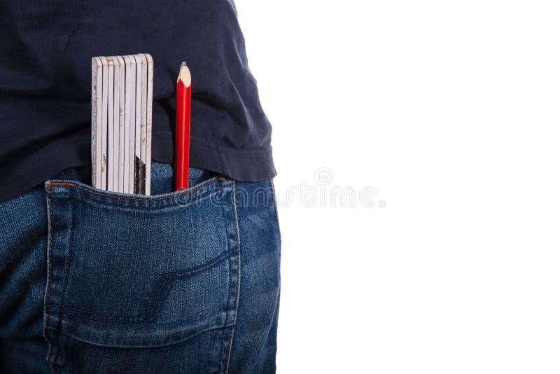 对牛仔裤的特写镜头有统治者和铅笔的 图库摄影