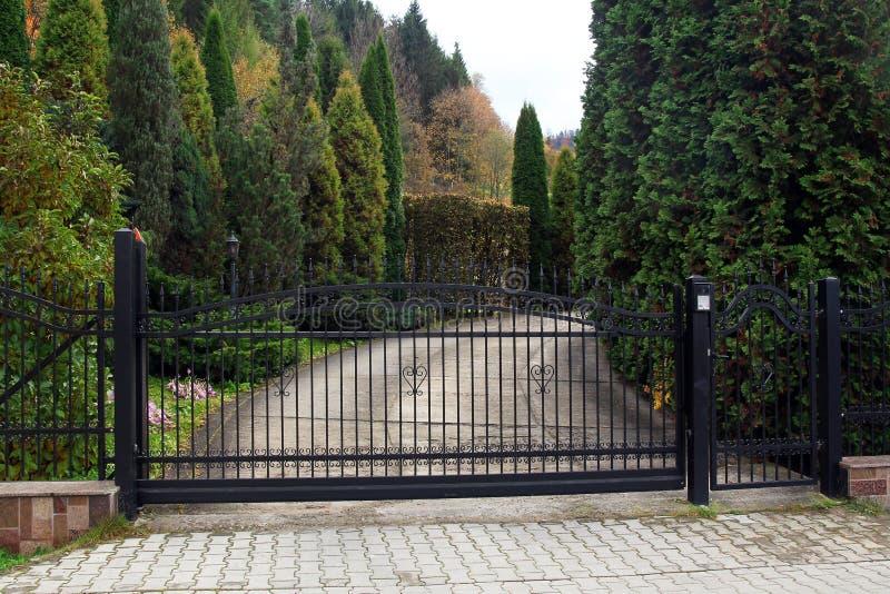对物产的黑加工的门与庭院在背景中 免版税库存照片