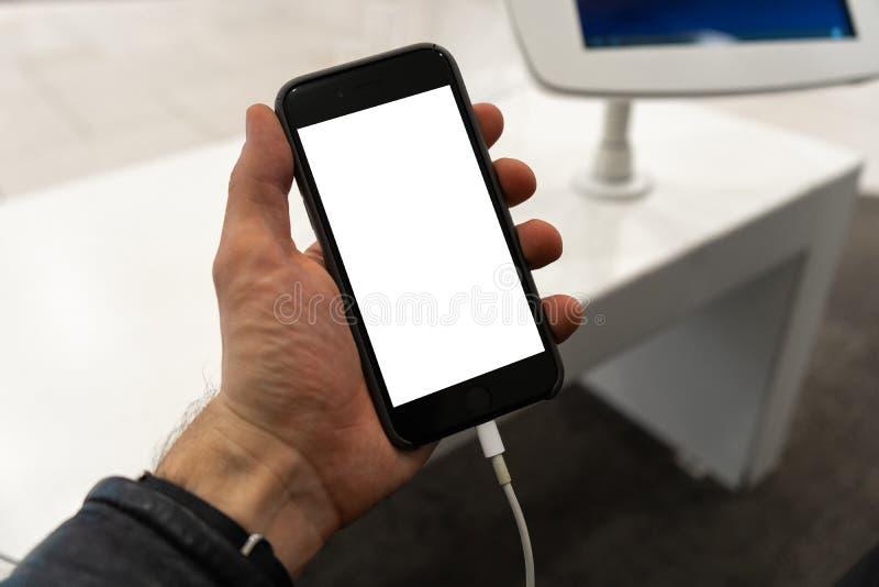 对电话的现实用途在举行与空您的广告和的文本的赠送阅本空间的人的手上-假装广告牌和 免版税库存照片