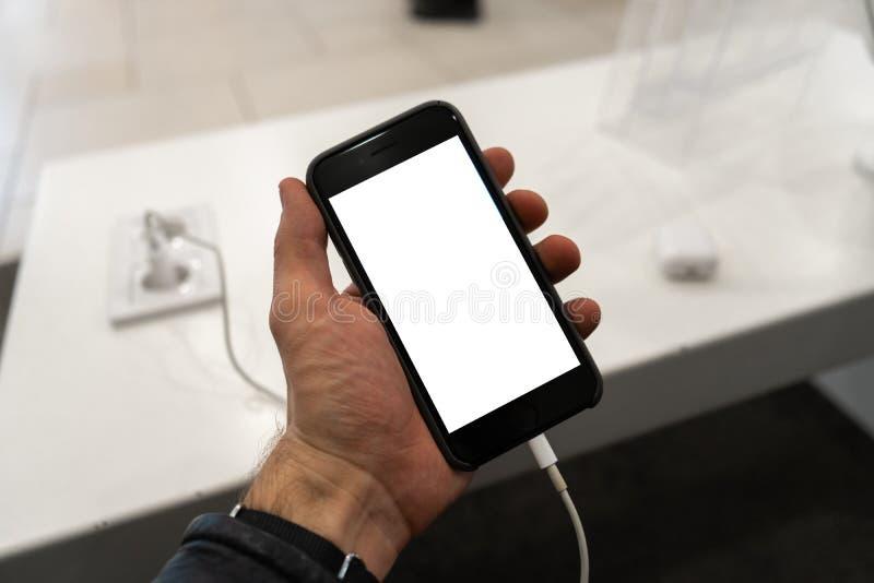 对电话的现实用途在举行与空您的广告和的文本的赠送阅本空间的人的手上-假装广告牌和 库存图片