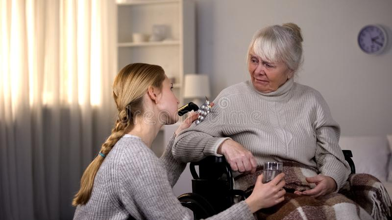 对病的祖母的妇女提供的医学,拿着药片和水玻璃 免版税库存照片
