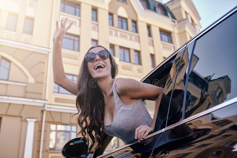 对看在车窗外面的某人的妇女wawing的手 免版税库存照片