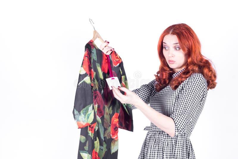 对礼服的价格失望的惊奇的可爱的妇女 免版税库存照片
