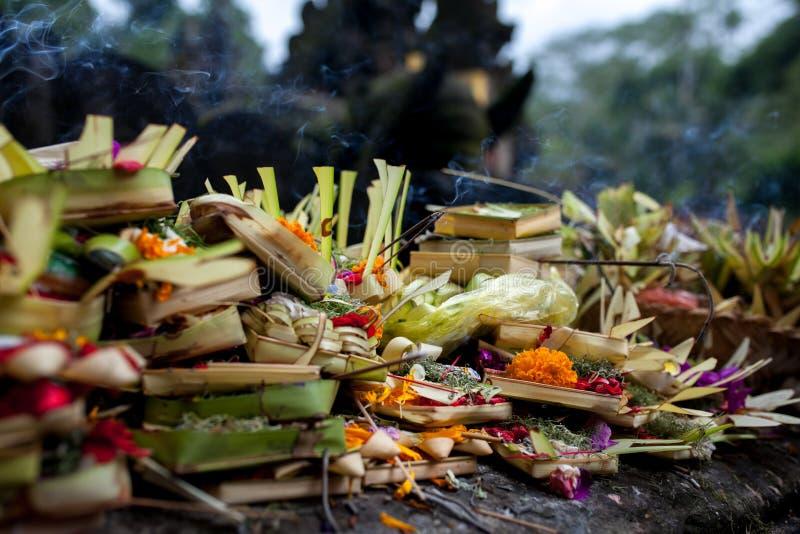 对神的传统巴厘语奉献物在有花和芳香棍子的巴厘岛 巴厘岛,印度尼西亚, Tirta Empul寺庙 免版税库存照片