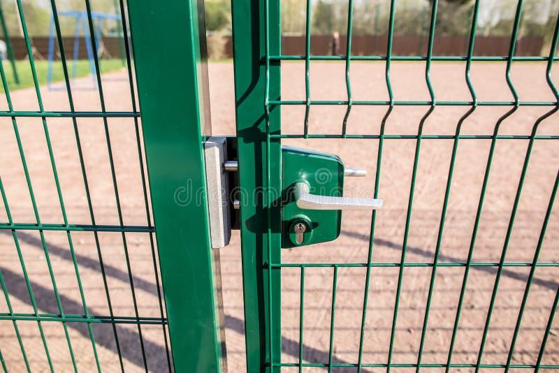 对篱芭操场和被焊接的小门的入口  免版税库存图片