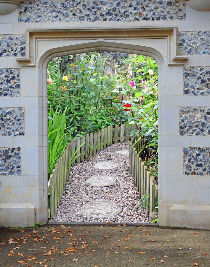 对美丽的庭院花植物的石曲拱门户门入口 免版税图库摄影
