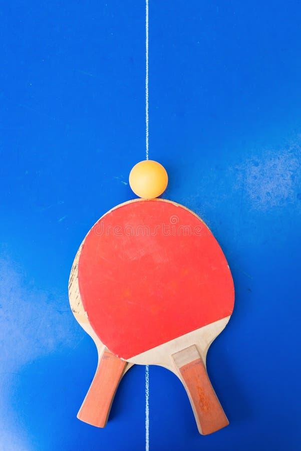 对老乒乓球球拍和一个球在蓝色球台上 库存图片