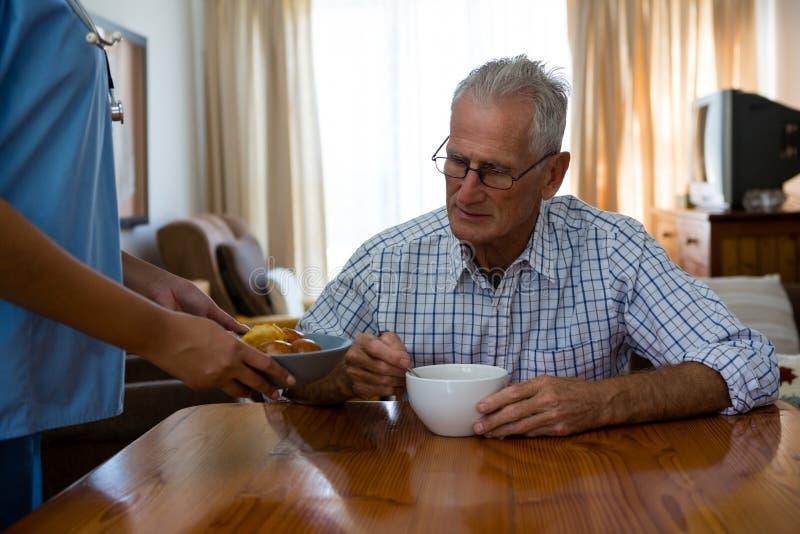 对老人的女性医生服务食物在老人院 免版税库存图片