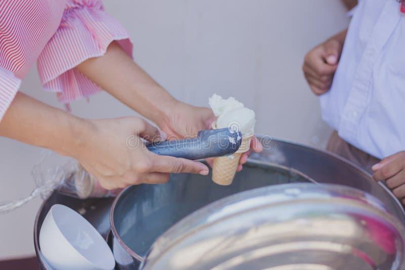 对老师` s handsGive冰淇凌的特写镜头对学生 库存照片