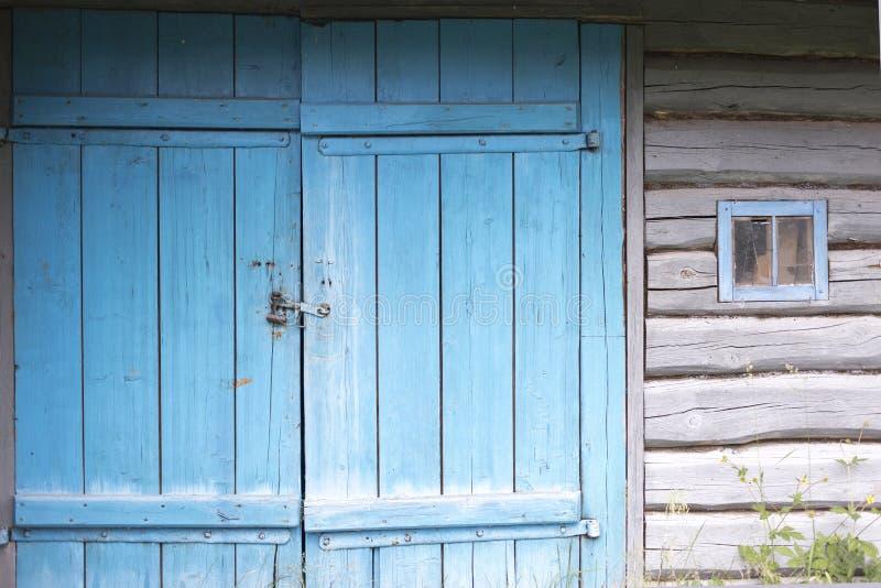 对老谷仓的老被绘的蓝色木门 蓝色木门w 库存照片