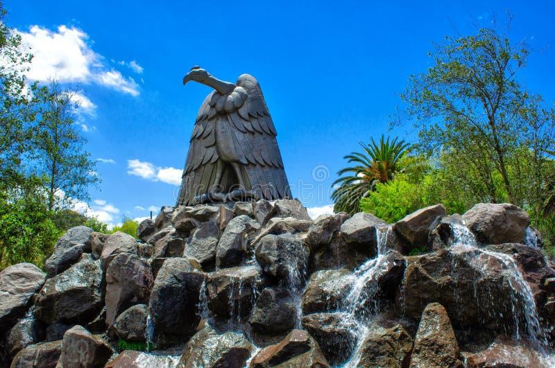 对老鹰的纪念碑在岩石 围拢由池塘 在La卡罗来纳州公园,基多 厄瓜多尔 免版税图库摄影