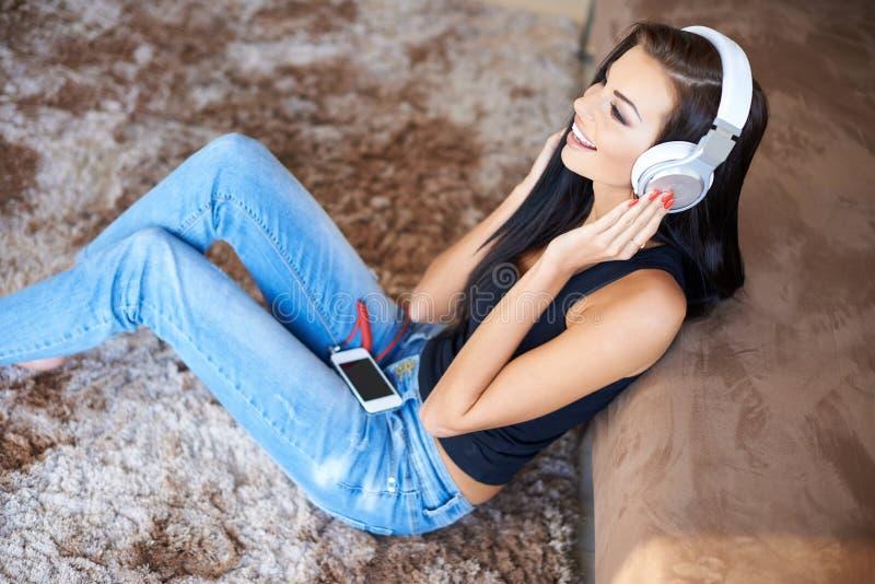 对耳机的坐的愉快的妇女听的音乐 免版税库存照片