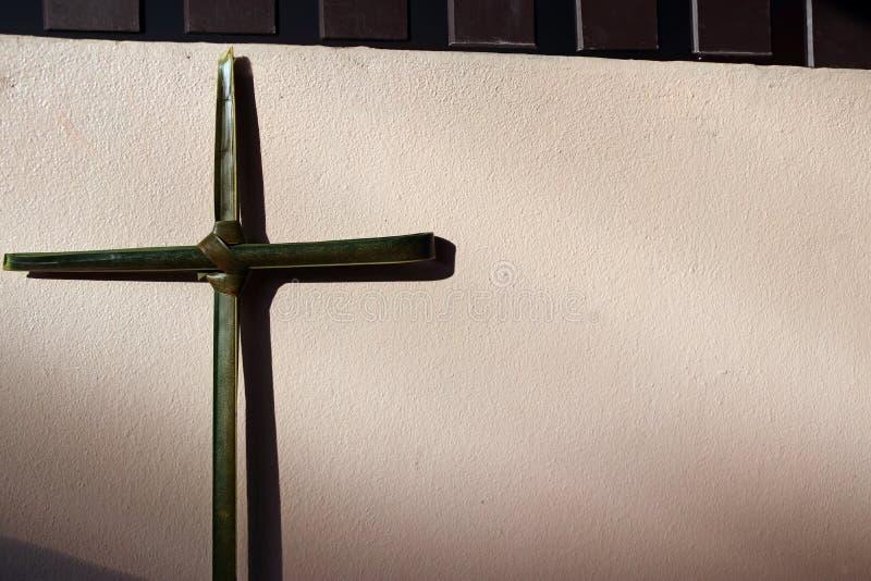 对耶稣受难象的棕榈叶集合十字架在有阳光和阴影的墙壁上 免版税库存图片