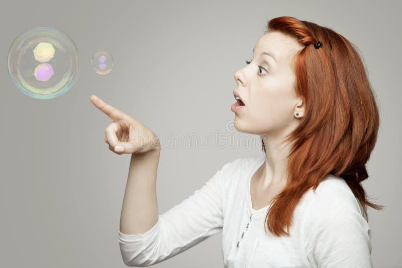 对肥皂泡和想知道的红发女孩查找 库存照片