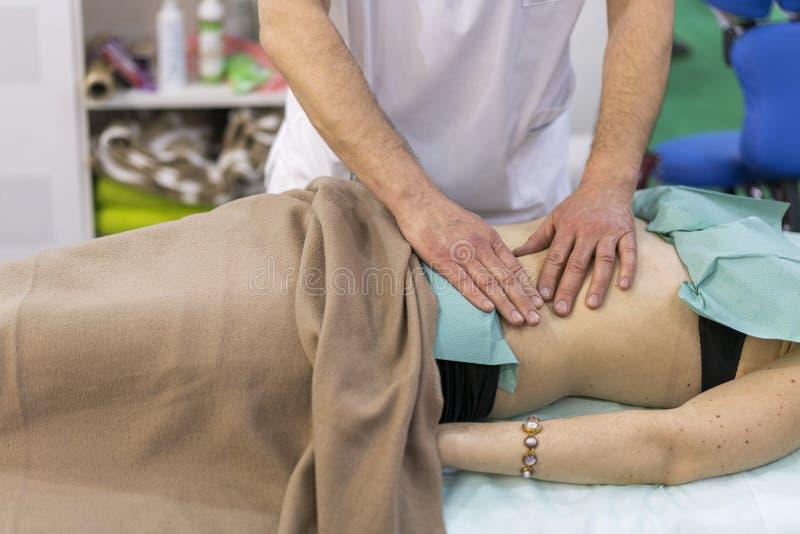 对肩膀按摩做的生理治疗师患者在一个医疗办公室 做男性后面的按摩专业男按摩师 免版税库存照片