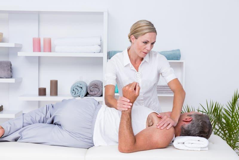 对肩膀按摩做的生理治疗师她的患者 免版税库存图片