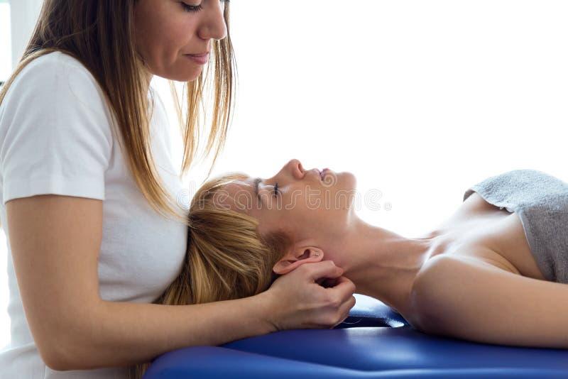 对脖子治疗做的年轻生理治疗师患者在物理疗法屋子 免版税库存图片